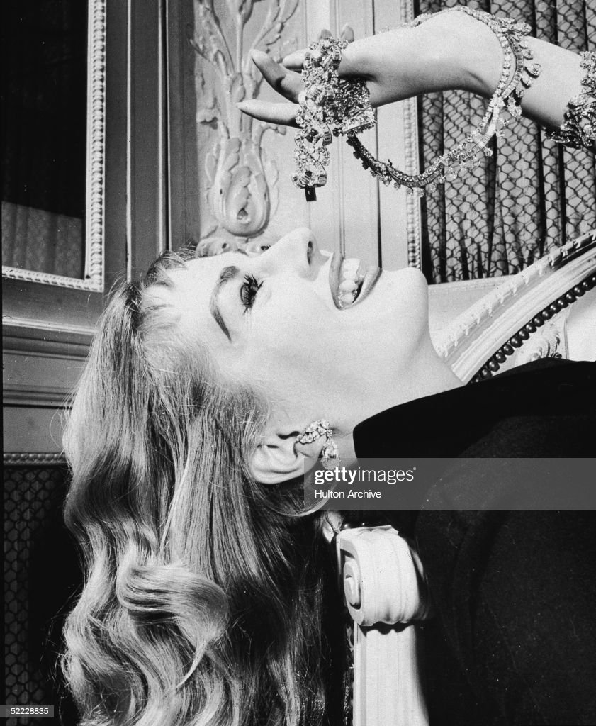 Swedish-born actress Anita Ekberg mimics the pose of eating grapes with pieces of diamond Cartier jewelry to show a love for diamonds, 1960s. She leans her head back over the arm of a loveseat and holds the jewelry over her mouth.
