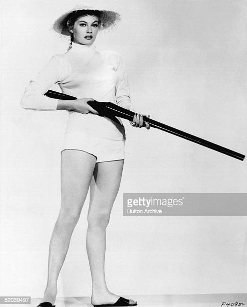 Swedishborn film actress Anita Ekberg dressed in a straw hat a highneck longsleeve shirt some very short shorts and sandals poses with a shotgun late...