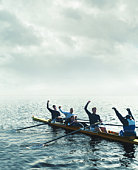 Sweep rowing crew, arms raised