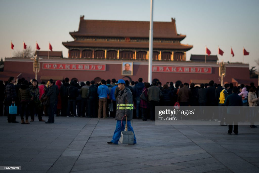 A sweeper walks past tourists as they watch the daily flag-lowering ceremony on Tiananmen Square in Beijing on March 4, 2013. Thousands of delegates from across China meet this week to seal a power transfer to new leaders whose first months running the Communist Party have pumped up expectations with a deluge of propaganda. AFP PHOTO / Ed Jones