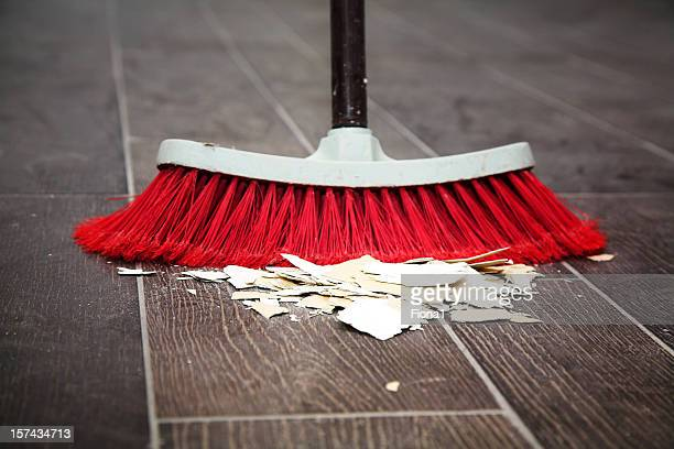 Sweeping the wooden floor with a broom