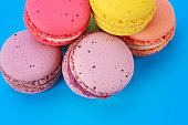 Sweet and colorful French macarons on blue background
