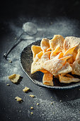 Sweet and golden angel wings with powdered sugar