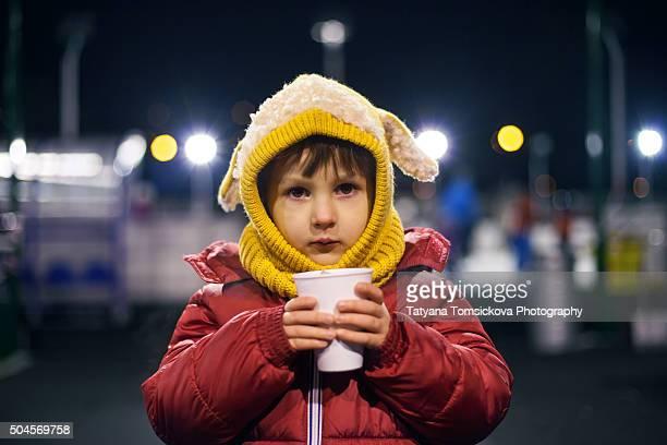 Sweet boy, drinking tea at night, wintertime outdoor