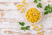 Sweet canned corn in a dish on a wooden background. Selective focus.