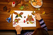 Sweet child, boy, applying leaves using glue while doing arts and crafts in school, autumn time