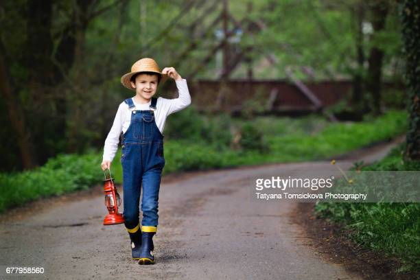 Sweet child, boy, holding red gas lamp, lantern, walking on rural road, looking for a way to go