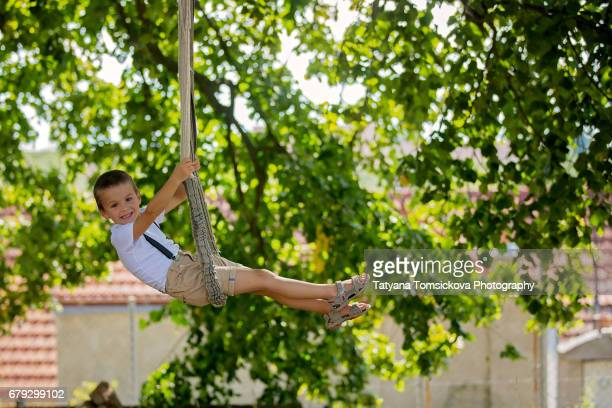 Sweet child, swinging on a rope swing summertime in the park