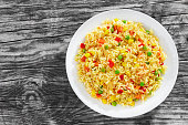 Sweet Corn, red bell pepper, green peas delicious  healthy Risotto on white plate on old wooden table, view from above