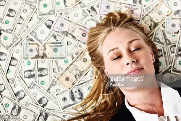 Sweet dreams as beautiful blonde sleeps on pile of dollars