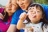 Sweet family playing bubbles in park joyfully