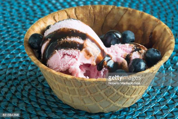 Sweet food strawberry ice cream with chocolate sauce and blueberries served in a waffle cup or small bowl