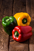 Sweet fresh red green yellow bell pepper on wooden table background