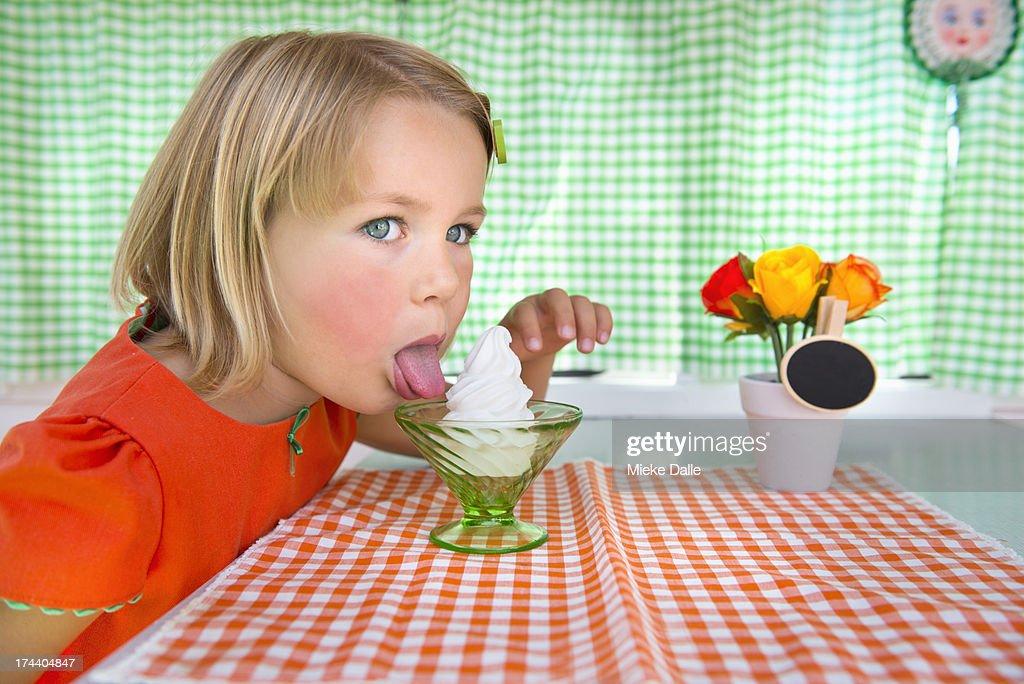 Sweet girl licking an ice-cream : Stock Photo