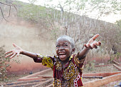Little African boy outdoors happy to get some rain, water for Africa symbol and concept - handsome sweet child posing outdoors.