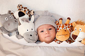 Sweet little baby lying on the bed surrounded of cute safari stuffed animals.