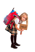 sweet little blonde schoolgirl asking for help carrying heavy backpack or school bag full causing stress and pain on back due to overweight isolated on white background