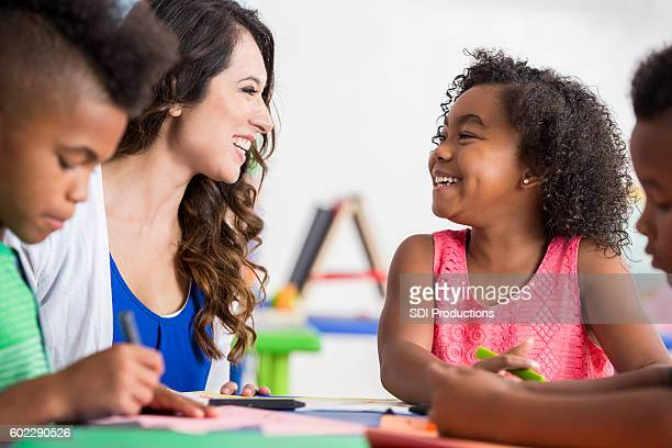 Sweet little girl laughing with her teacher in classroom