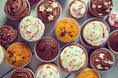 Multiple colorful nicely decorated muffins on a wooden background, top view