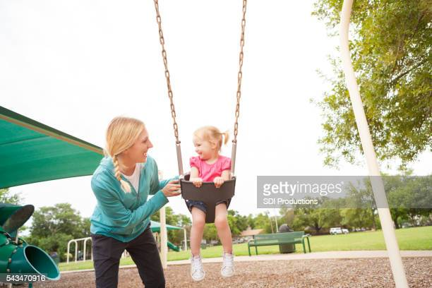 Sweet mom and daughter having fun on the swings