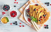 Sweet pancakes on milk with honey and fresh berries, healthy breakfast concept
