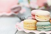 Saucer of fresh pastel colored macarons. Extreme shallow depth of field with selective focus on foreground.