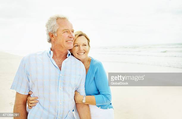 Sweet picture of older couple embracing on a beach