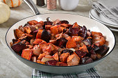 Beet and yam hash with onions in a skillet