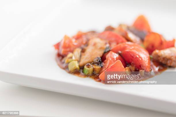 Sweet sliced pork with tomatoes and spring onions.