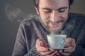 Young man enjoying the smell of his hot beverage, tea or coffee, anticipating the sweet taste