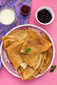 Sweet thin pancakes crepes served with raspberry jam and blueberries