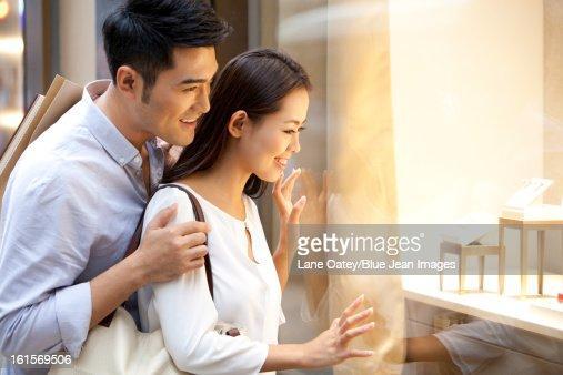 Sweet young couple doing window shopping in Hong Kong