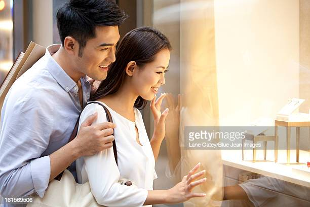 Sweet young couple doing window shopping in Hong Kong