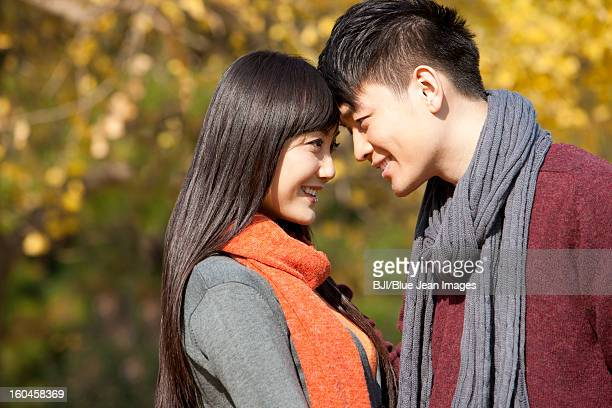 Sweet young couple in love face to face outdoors in autumn