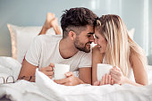 Young beautiful couple drinking coffee in bed at morning.