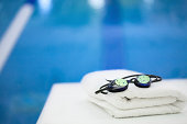 Reflective goggles with beads of water on them, sitting besides a swimming pool on a clean, white, nicely folded towel. Illustrates health, fitness,  and a clean lifestyle with no person in the image.