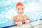 Smiling schoolgirl in swim-cap looking out of water while training in swimming-pool
