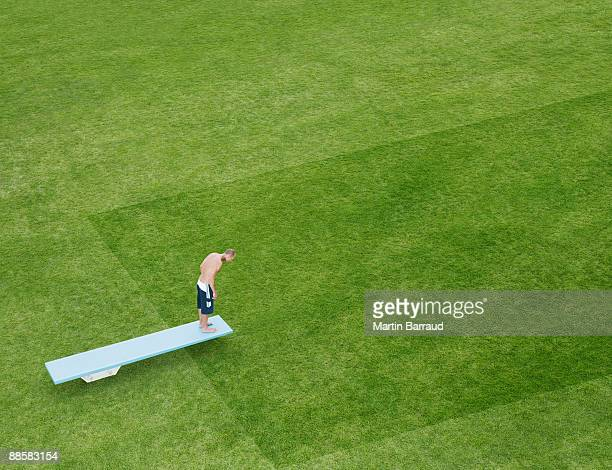 Swimmer about to jump off diving board into grass