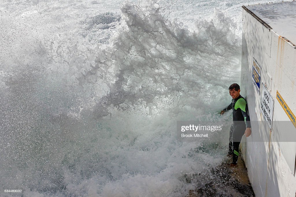 A swimmer at Bronte Beach Ocean Pool ducks for cover as large waves hit the coast.