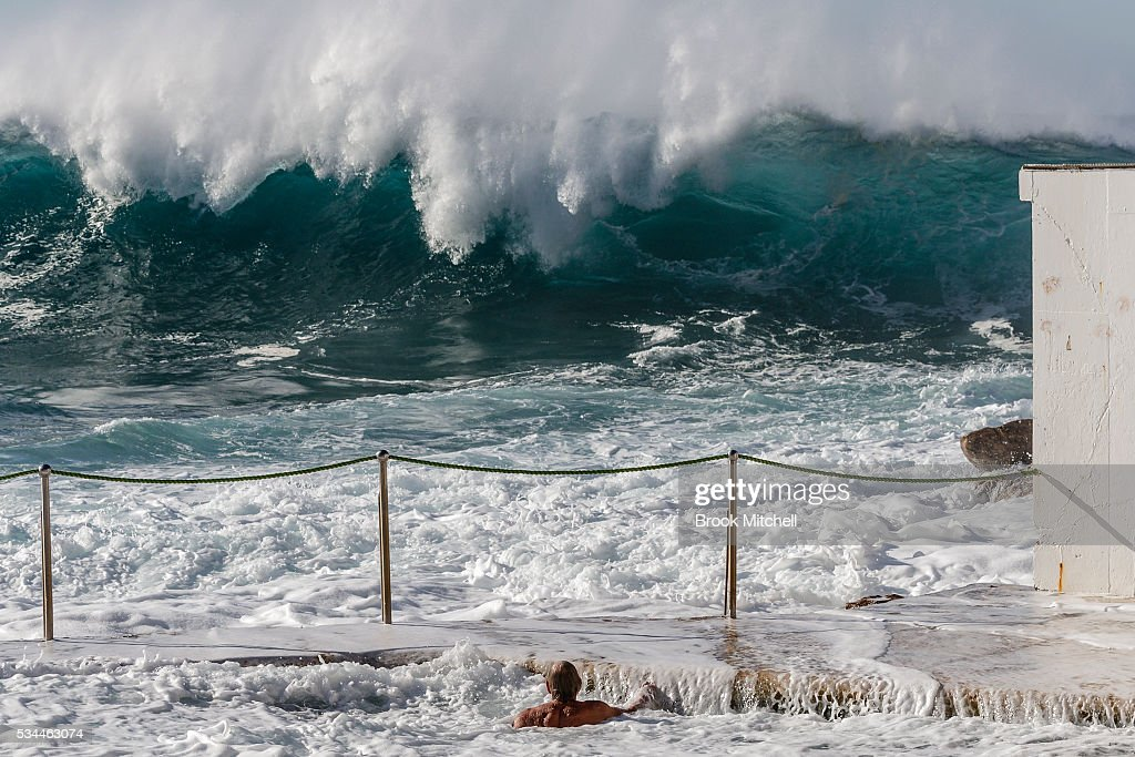 A swimmer at Bronte Beach Ocean Pool watches as large waves crash across the beach on May 25, 2016 in Sydney, Australia. All Sydney beaches were closed to swimmers today as large waves pounded the coast.