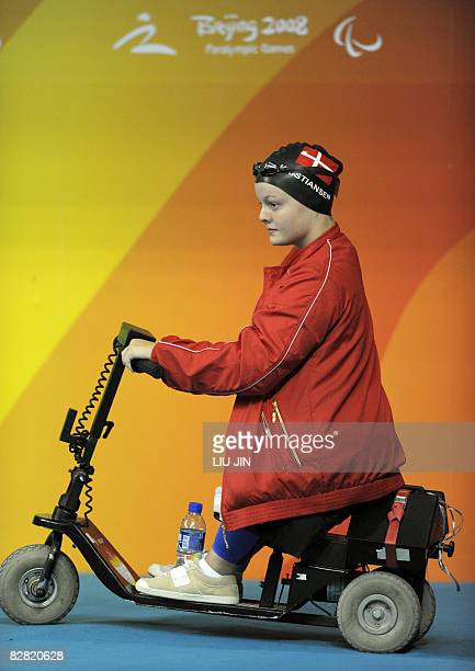 swimmer Cecilie Kristiansen of Denmark drives a scooter to the women's 50m freestyle S4 final during the 2008 Beijing Paralympic Games at the...