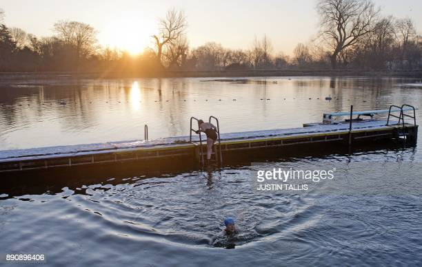 A swimmer climbs from a snow covered jetty into the ice cold water at Highgate Men's Bathing Pond in north London on December 12 at sunrise on a...