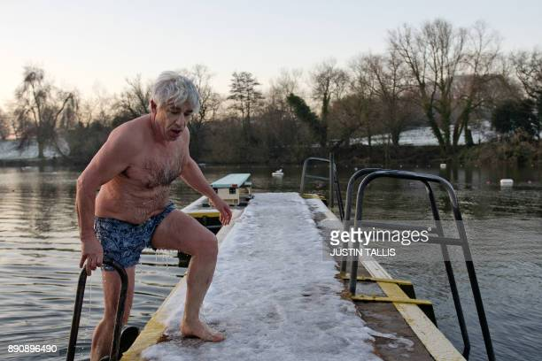 A swimmer climbs out of the ice cold water at Highgate Men's Bathing Pond in north London on December 12 at sunrise on a freezing winter morning /...