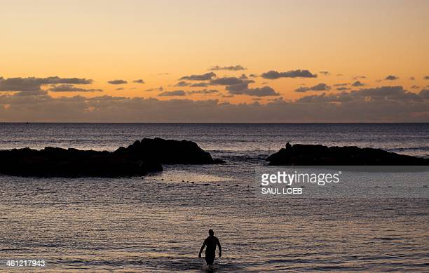 A swimmer comes in to the beach from the Pacific Ocean at sunset in the town of Kapolei on the island of Oahu in Hawaii on January 6 2014 AFP PHOTO /...