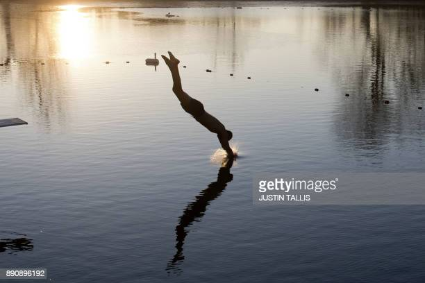 A swimmer dives into the ice cold water at Highgate Men's Bathing Pond in north London on December 12 at sunrise on a freezing winter morning PHOTO /...