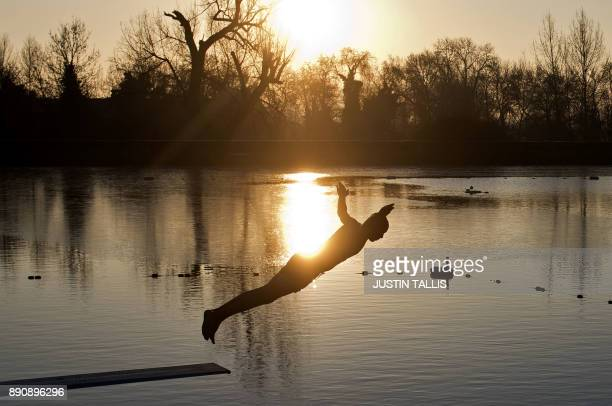 A swimmer dives into the ice cold water at Highgate Men's Bathing Pond in north London on December 12 at sunrise on a freezing winter morning / AFP...