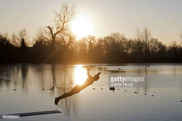 A swimmer dives into the ice cold water at the Highgate Men's Bathing Pond in north London on December 12 at sunrise on a freezing winter morning /...