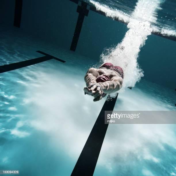 Nuotatore immersioni dopo il salto in piscina
