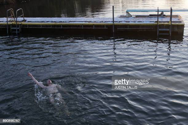 A swimmer does back stroke in the ice cold water at Highgate Men's Bathing Pond in north London on December 12 at sunrise on a freezing winter...