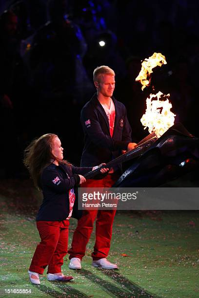 Swimmer Eleanor Simmonds and athlete Jonnie Peacock light torches from the flame of the Paralympic cauldron as it is extinguished during the closing...